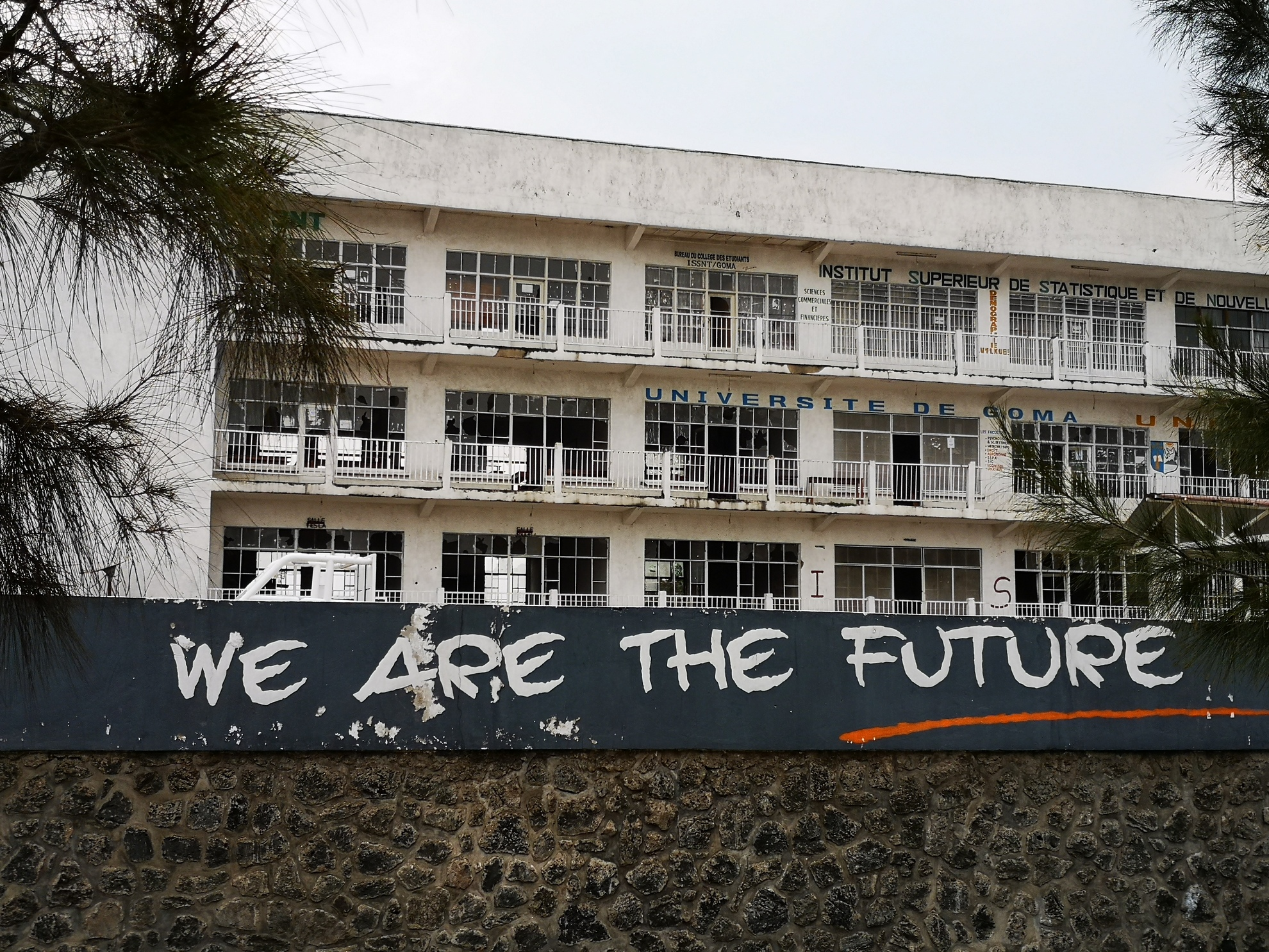 """Graffiti, """"We are the future"""" is spray painted on the wall in front of the University of Goma. In the background, half of the windows in the five-story building are broken."""