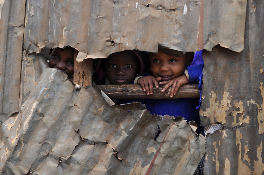 Kenyan children peek through a broken tin wall