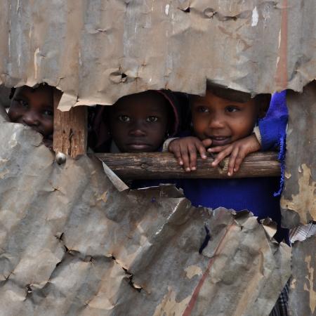 Kenyan children peek through a broken tin wall