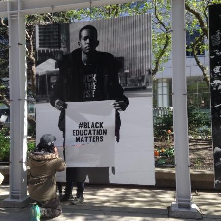 Man repairing slashed Black Education Matters photo