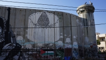 Israel security wall with painting of a Christmas tree surrounded by the wall