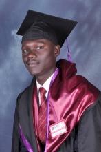 Sam in cap and gown, a graduate of Uganda Christian University