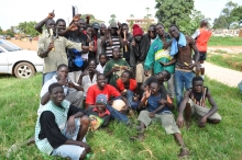25 street youth in Kampala, smiling and posing for the camera